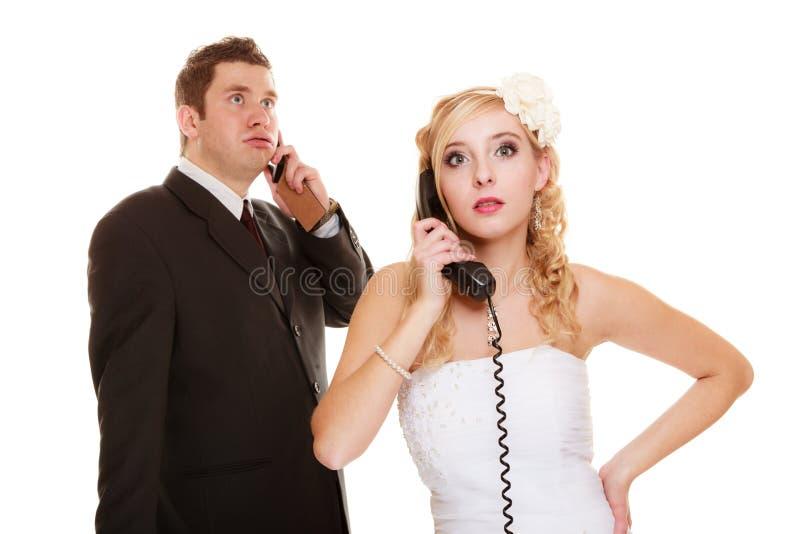 El casarse. Novia enojada y novio que hablan en el teléfono imagenes de archivo