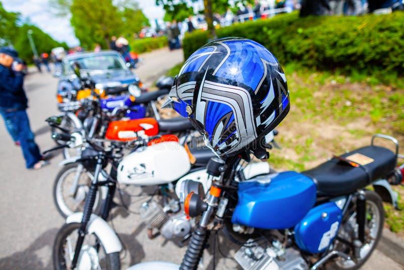 El casco azul cuelga en la moto fotos de archivo