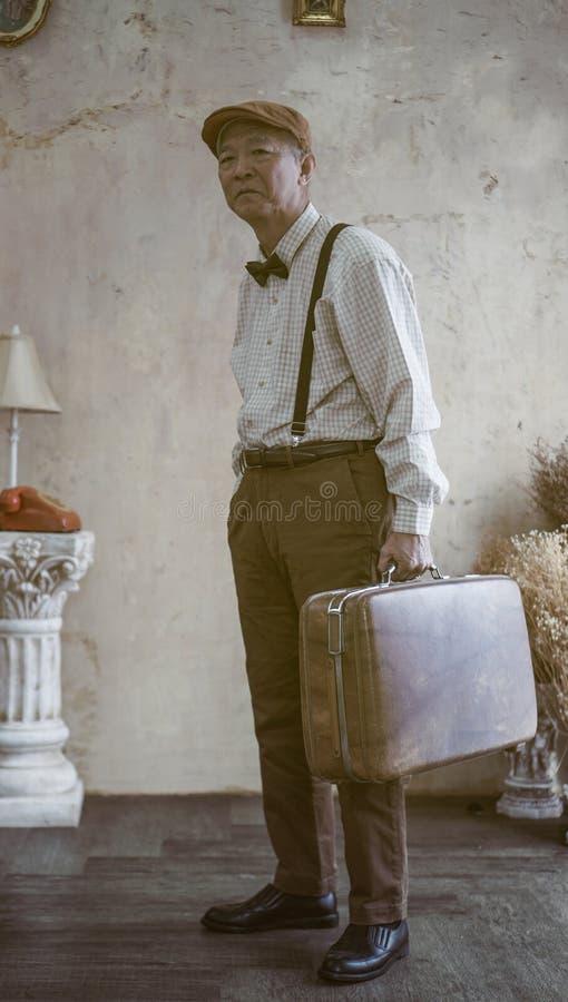 El casquillo plano asiático del desgaste de hombre mayor de la moda retra del vintage y suspende imagen de archivo