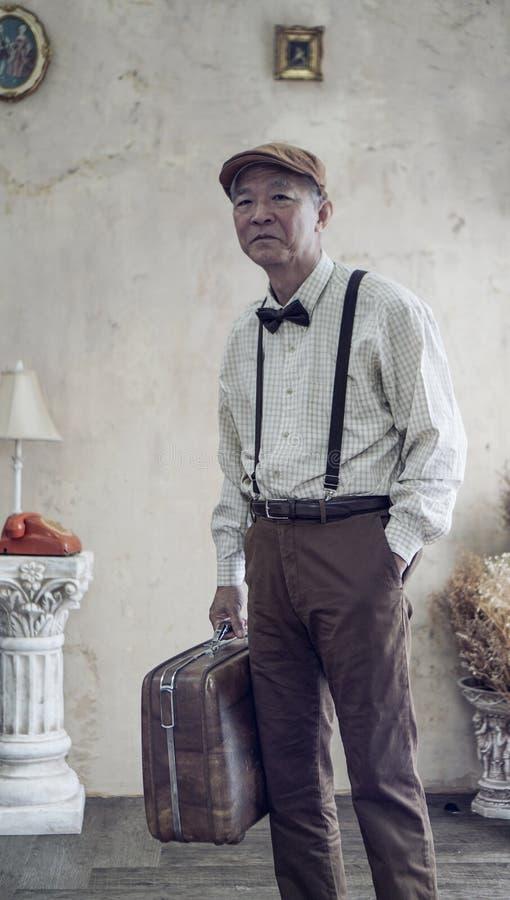 El casquillo plano asiático del desgaste de hombre mayor de la moda retra del vintage y suspende imágenes de archivo libres de regalías