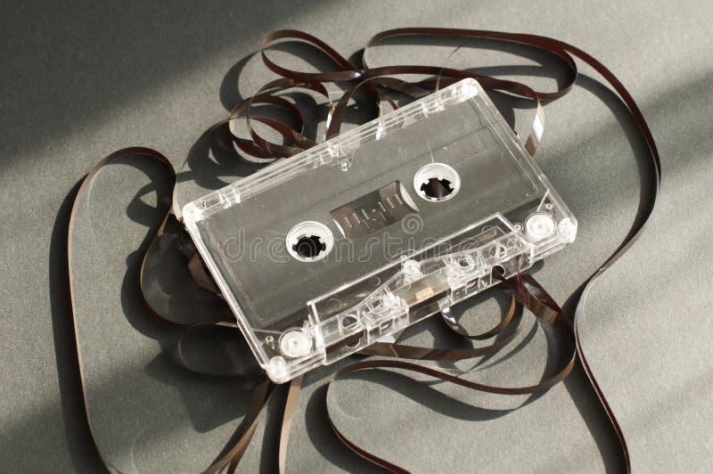 El cassette de la cinta de audio con restado hacia fuera sujeta con cinta adhesiva fotos de archivo