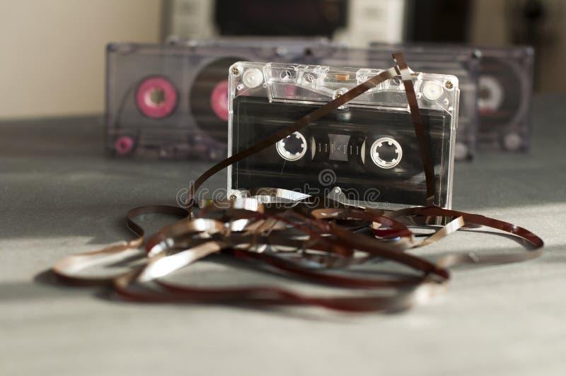 El cassette de la cinta de audio con restado hacia fuera sujeta con cinta adhesiva foto de archivo