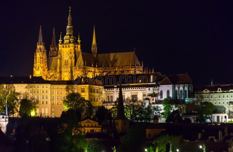 El castillo de Praga con Charles Bridge y enciende para arriba noche fotos de archivo libres de regalías