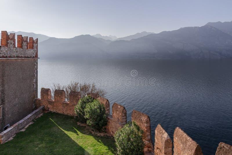 El castillo medieval IL Castello Scaligero di Malcesine y la visión de Scaliger de las montañas en la niebla del lago Garda en Ma imagen de archivo