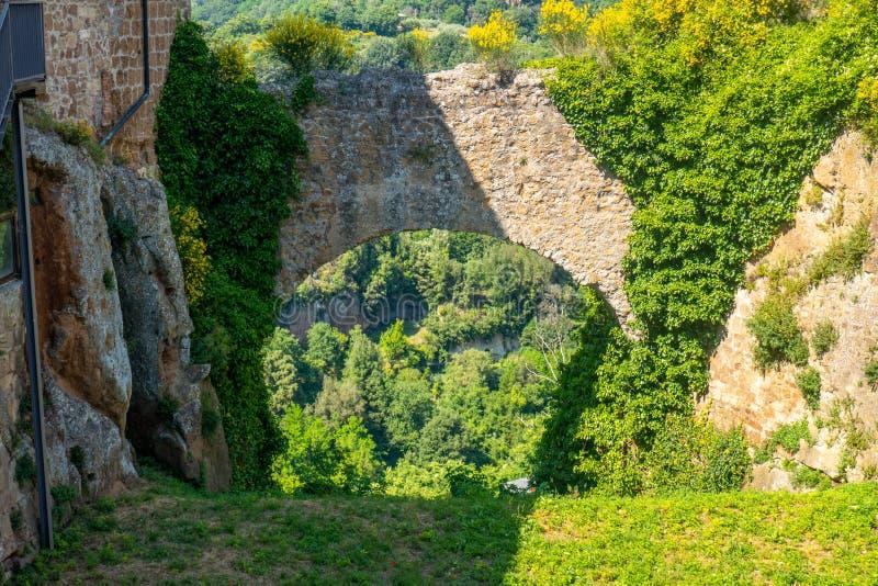 El castillo rocas de la pequeña ciudad medieval de Sorano, Toscana, Italia, con colinas y cielo azul en segundo plano fotos de archivo