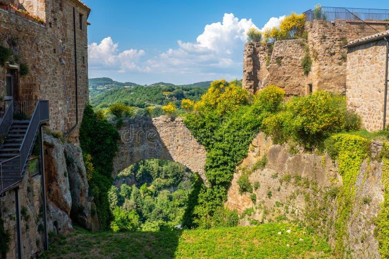 El castillo rocas de la pequeña ciudad medieval de Sorano, Toscana, Italia, con colinas y cielo azul en segundo plano imagenes de archivo