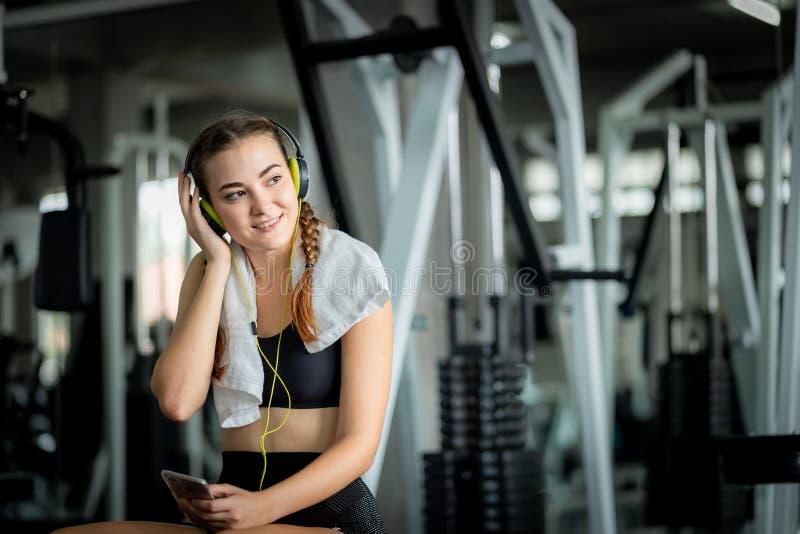 El caucásico atractivo joven de la mujer que se sienta y que escucha la música por los auriculares conecta con el teléfono elegan foto de archivo libre de regalías