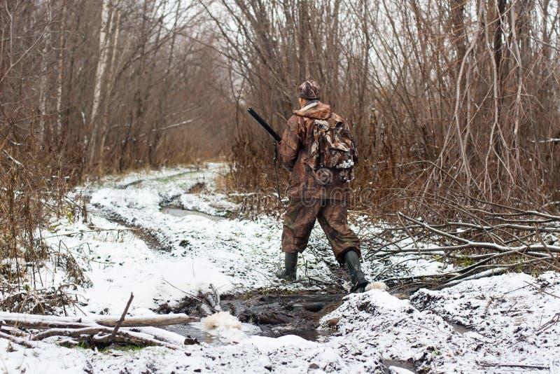 El cazador con el arma de la caza cruza la corriente en invierno fotos de archivo libres de regalías