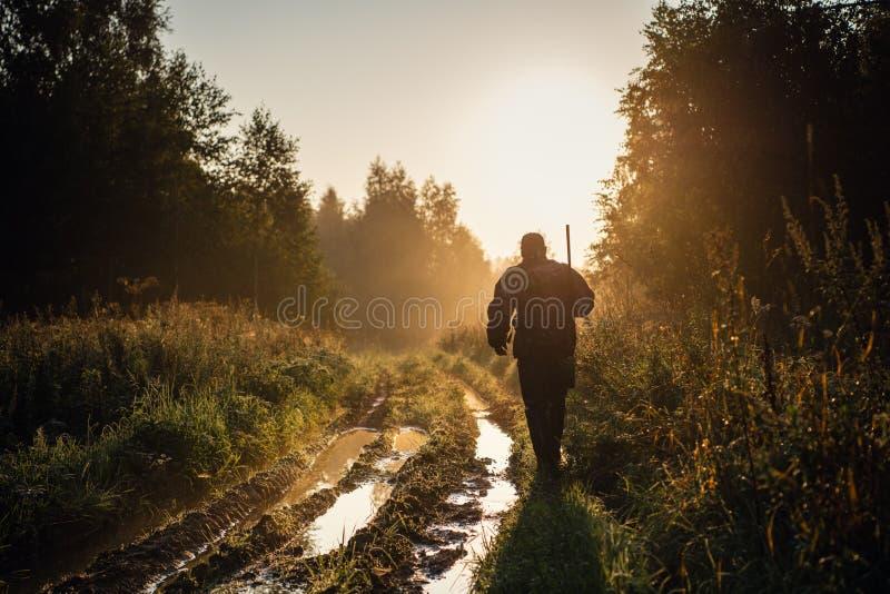 El cazador de cosechas camina por el camino del bosque Cazadora de rifles silueta en bello atardecer o amanecer Fusil de puntería imagen de archivo libre de regalías