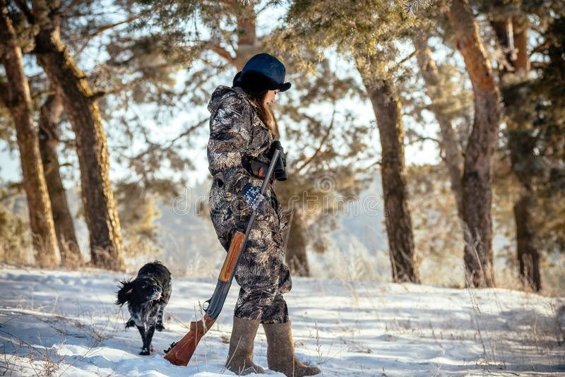 El cazador de la muchacha con los prismáticos en el bosque, demostraciones persigue la dirección s foto de archivo