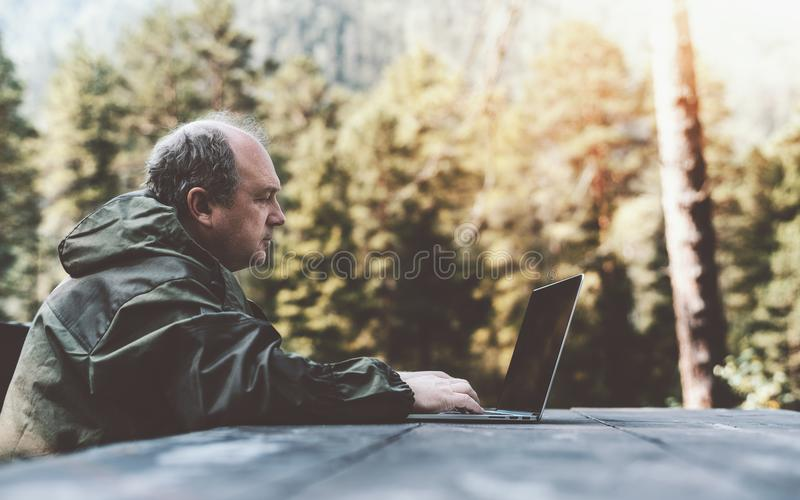 El cazador está utilizando su netbook al aire libre fotografía de archivo