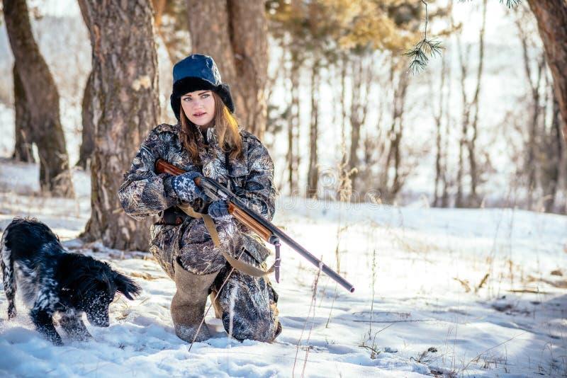 El cazador femenino en camuflaje viste listo para cazar, sosteniendo el arma a imagenes de archivo