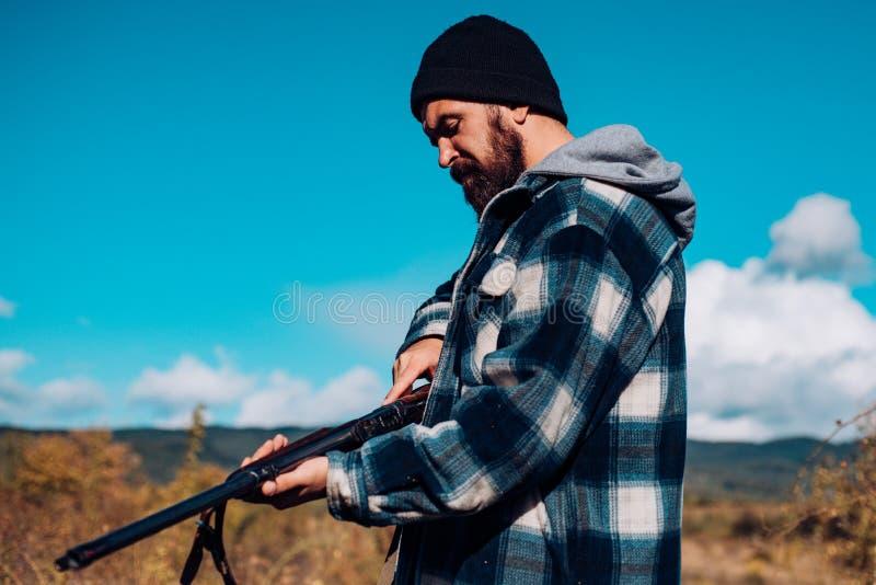El cazador pasa la caza del ocio Búsqueda del equipo para los profesionales La caza es afición masculina brutal para los cazadore fotografía de archivo