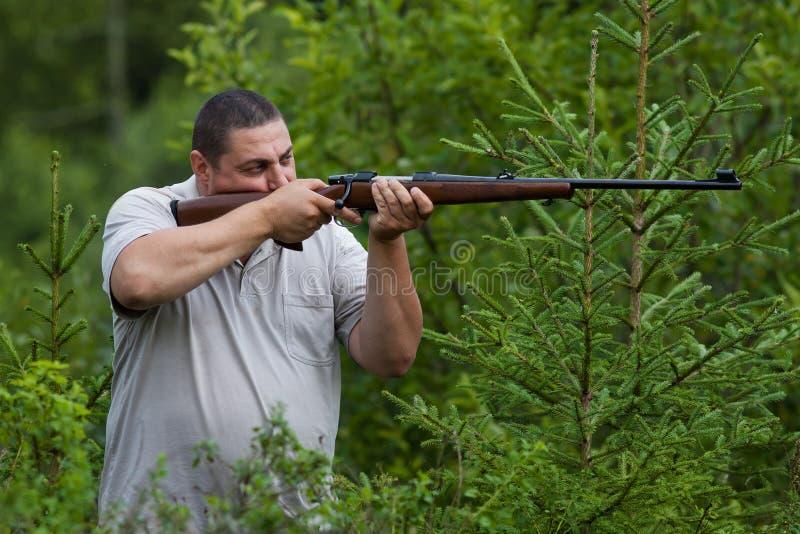 El cazador que apunta de un rifle fotografía de archivo libre de regalías
