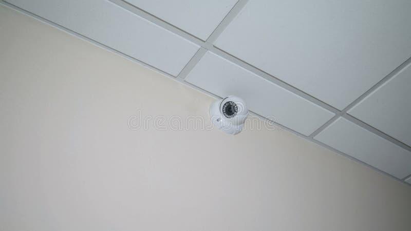El CCTV está situado en la pared bajo techo, surve redondo blanco imagen de archivo
