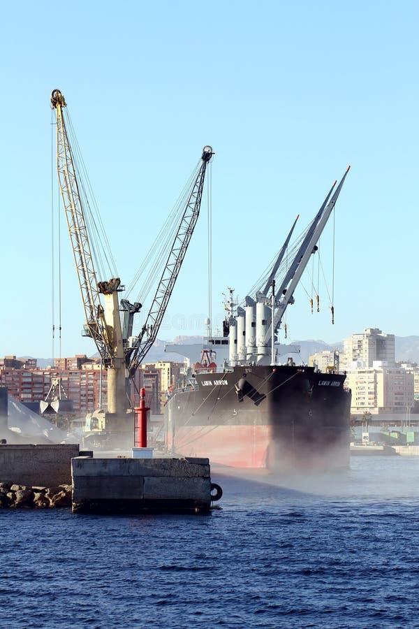 El cemento del cargamento de la FLECHA del granelero LAWIN con las grúas en el puerto de Alicante fotografía de archivo libre de regalías