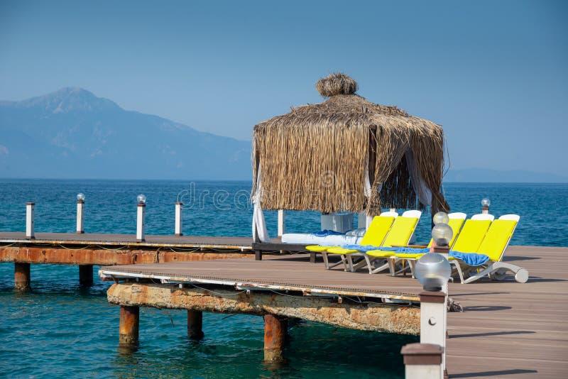 El cenador de madera está en una playa soleada Cielo azul y montaña en el fondo Vacaciones y día de fiesta en concepto de la play fotos de archivo