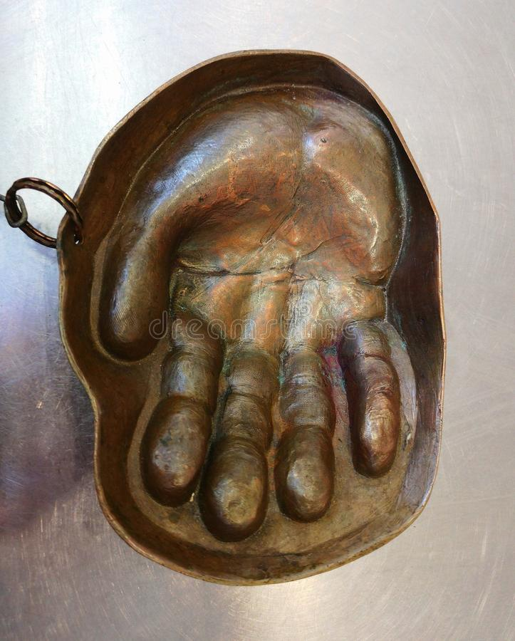 El cenicero de cobre bajo la forma de mano para recibir acuña imagenes de archivo