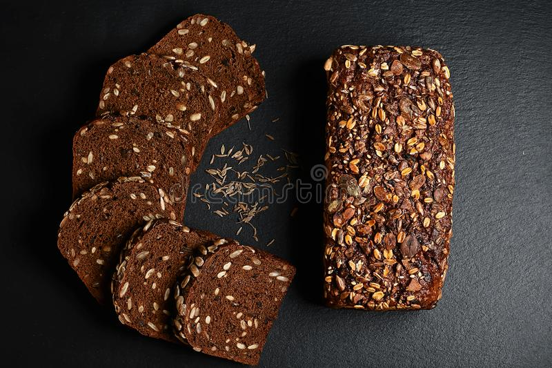 El centeno oscuro, pan con las semillas de girasol, pan entero, granos del cereal del comino en una pizarra oscura del fondo sube fotos de archivo