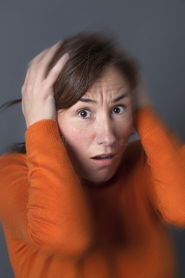 El centro asustado envejeció los oídos cerrados de la mujer que expresaban pánico y miedo imagen de archivo libre de regalías