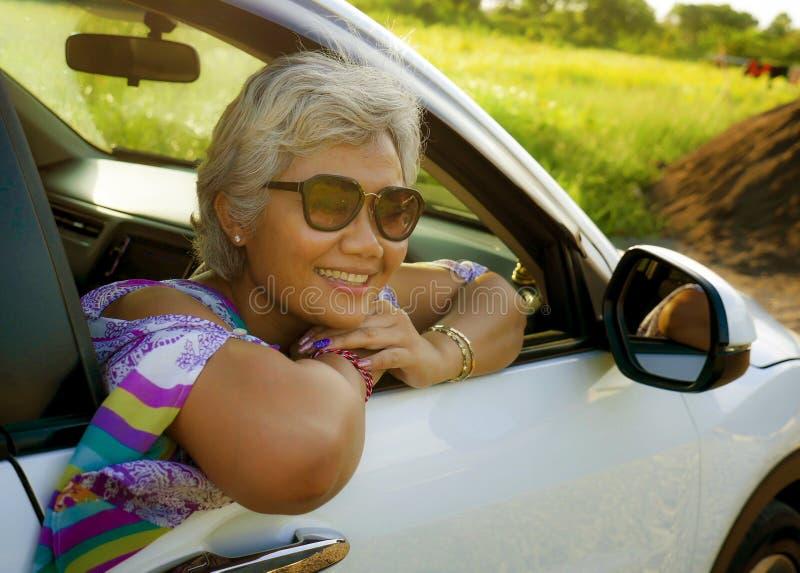 El centro atractivo y feliz envejeci? a la mujer indonesia asi?tica 40s o 50s con el pelo gris y la sonrisa hermosa que se sentab imagen de archivo libre de regalías