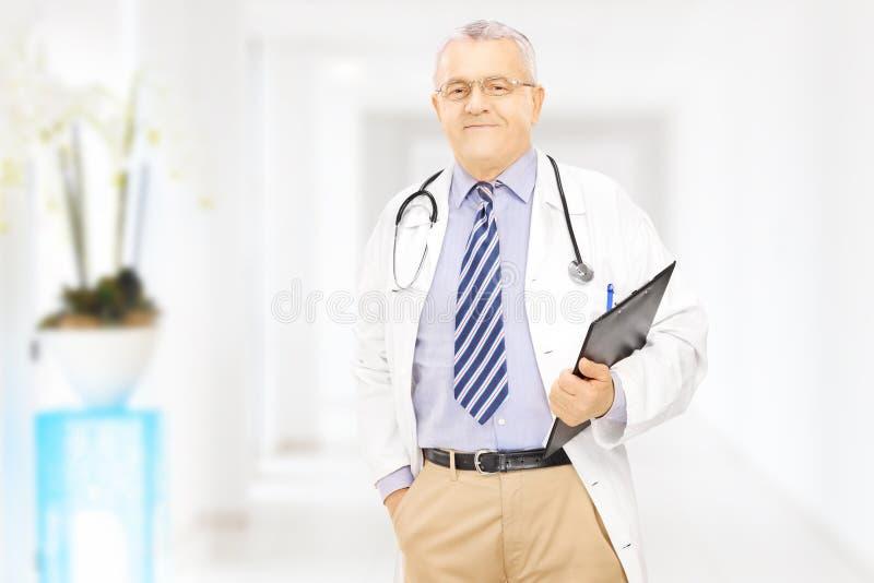 El centro confiado envejeció al doctor que sostenía un tablero en un hospital imagenes de archivo