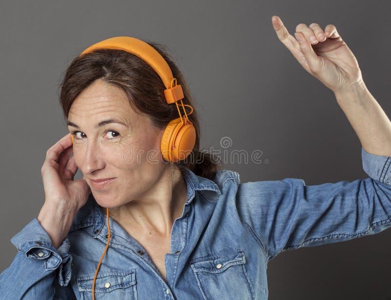 El centro de la diversión envejeció a la mujer que escuchaba la música bienestar feliz fotos de archivo libres de regalías