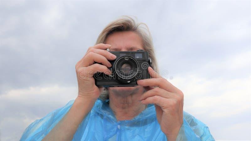 El centro envejeció al fotógrafo de sexo femenino que tomaba las fotos al aire libre foto de archivo