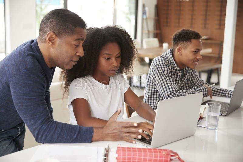El centro envejeció al hombre afroamericano que ayudaba a sus niños adolescentes a hacer su preparación usando los ordenadores po fotografía de archivo libre de regalías