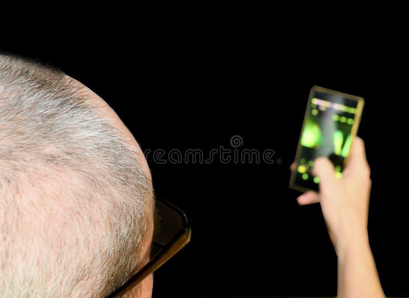 El centro envejeció al hombre con los vidrios que se sentaban en una butaca Hombre maduro con el teléfono móvil en fondo negro Co fotografía de archivo