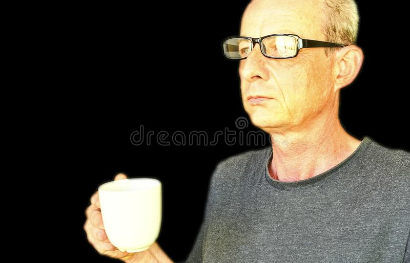 El centro envejeció al hombre con los vidrios que sostenían una taza blanca Retrato del hombre maduro en fondo negro Copie el esp foto de archivo