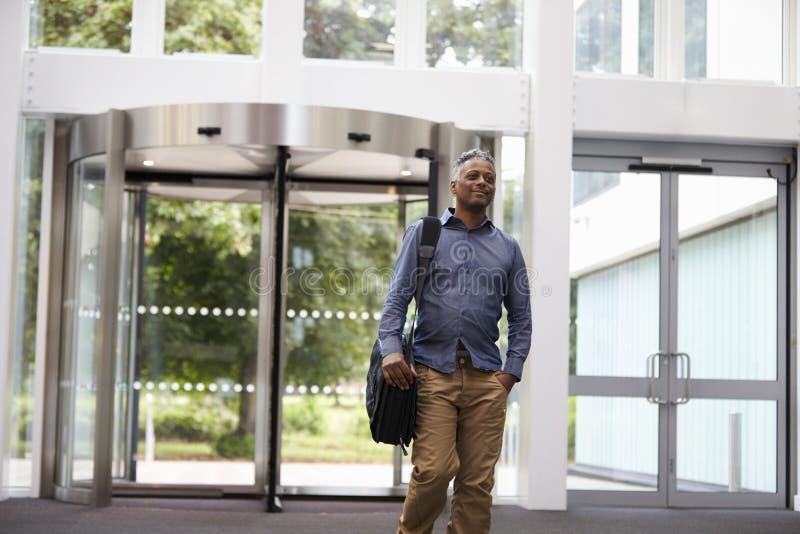 El centro envejeció al hombre negro en el salón de un edificio moderno grande fotografía de archivo