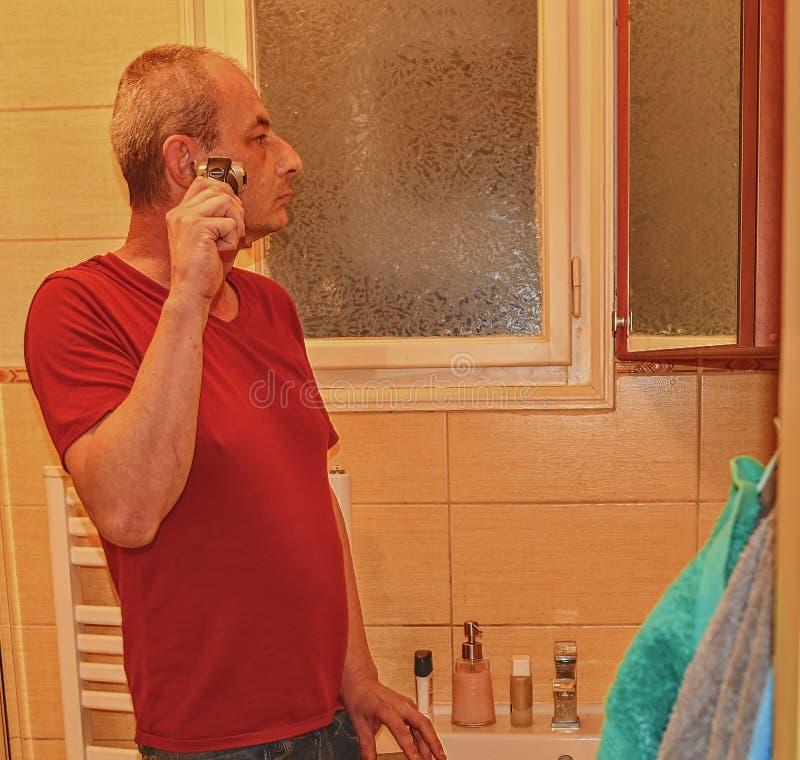 El centro envejeció al hombre que afeitaba en un cuarto de baño, usando la maquinilla de afeitar eléctrica Concepto mayor Hombre  foto de archivo