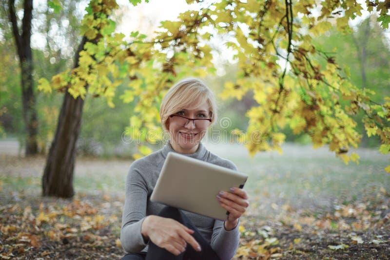 El centro envejeció a la mujer caucásica se sienta solamente en el parque de oro del otoño con la tableta, sonriendo Ropa de spor foto de archivo
