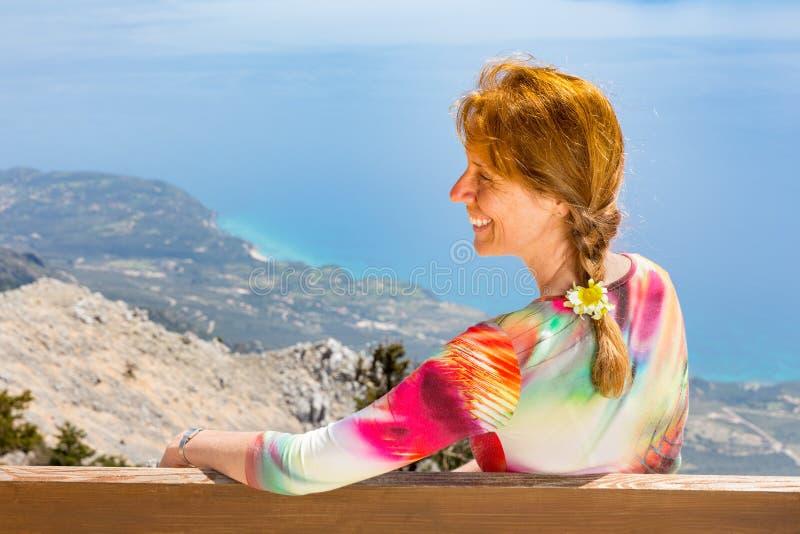 El centro envejeció a la mujer que miraba el mar y la costa foto de archivo