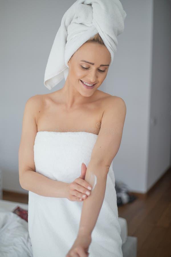 El centro envejeció a la mujer rubia hermosa hidrata el brazo después de la ducha fotos de archivo