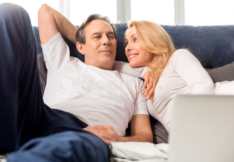 El centro envejeció los pares que miraban uno a y que mentían en cama en casa foto de archivo libre de regalías