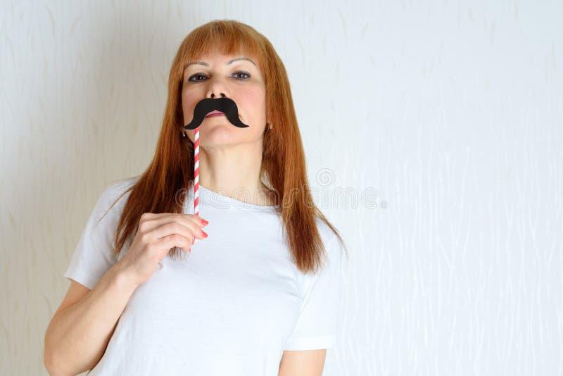 El centro feliz atractivo envejeció a la mujer que se divertía con un bigote falso en el palillo fotos de archivo