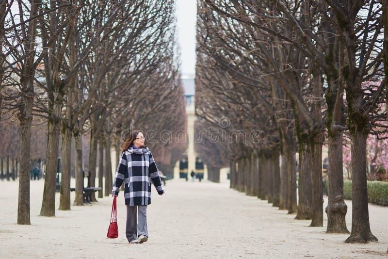 El centro hermoso envejeció a la mujer que caminaba en parque parisiense imagenes de archivo