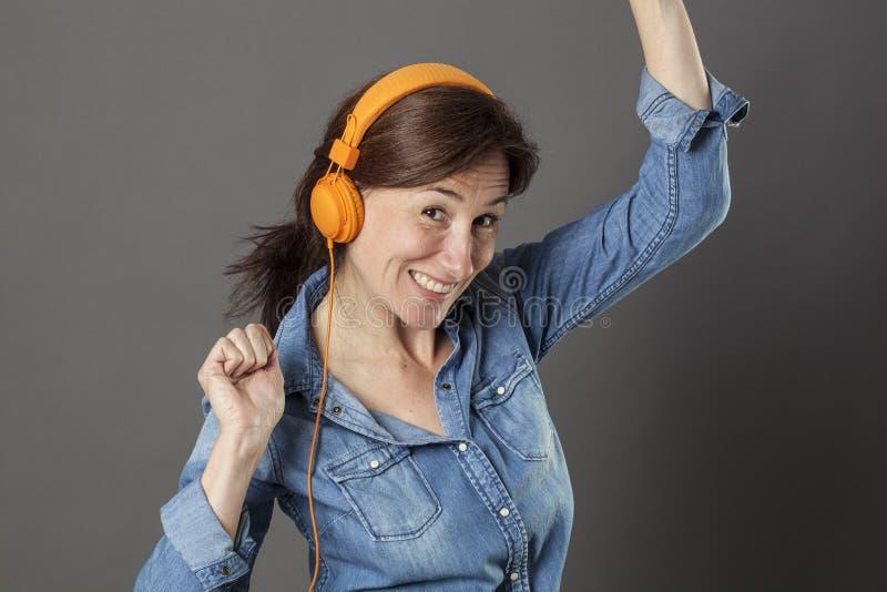El centro hermoso feliz envejeció el baile de la mujer en escuchar la música foto de archivo