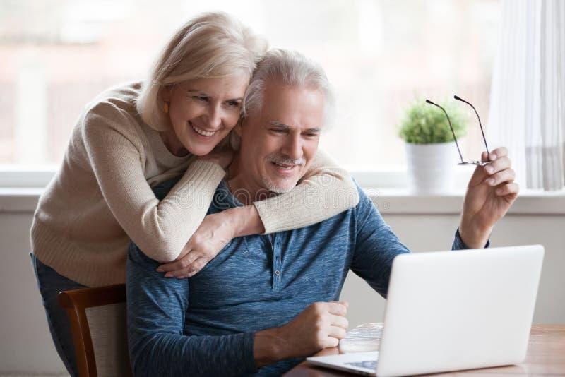 El centro mayor envejeció los pares felices que abrazaban usando el ordenador portátil junto fotos de archivo