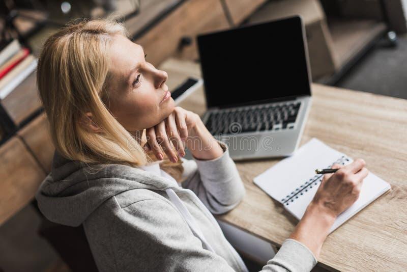 el centro pensativo envejeció a la mujer que tomaba notas y que usaba el ordenador portátil en casa fotos de archivo
