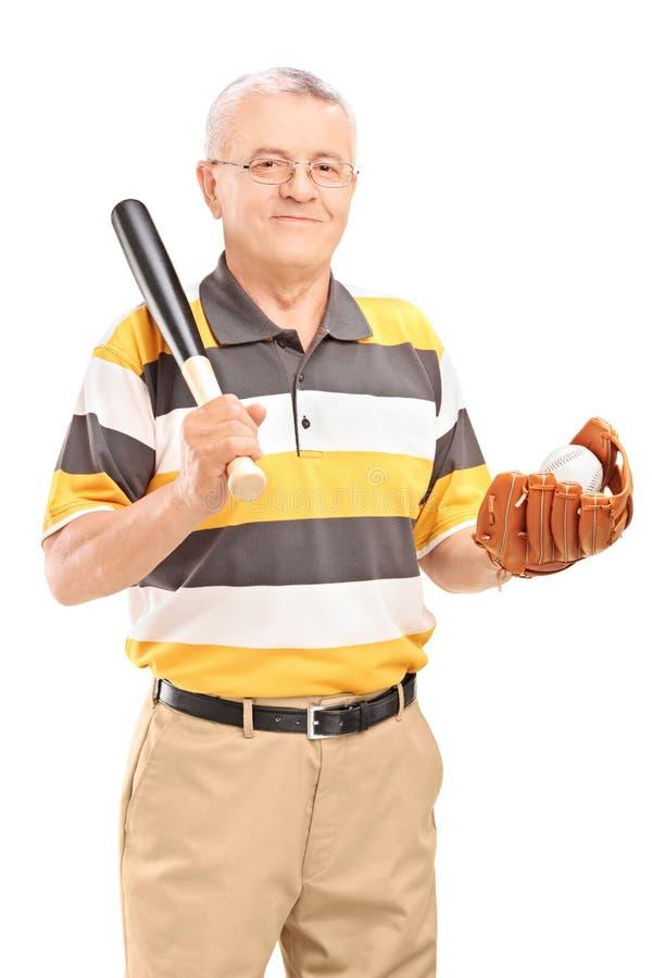 El centro sonriente envejeció al hombre que sostenía un bate de béisbol y un guante de madera fotos de archivo libres de regalías