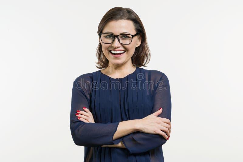 El centro sonriente envejeció a la mujer con los brazos doblados en el fondo blanco fotos de archivo libres de regalías