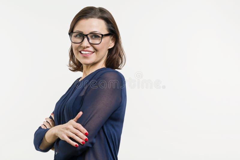 El centro sonriente envejeció a la mujer con los brazos doblados en el fondo blanco foto de archivo