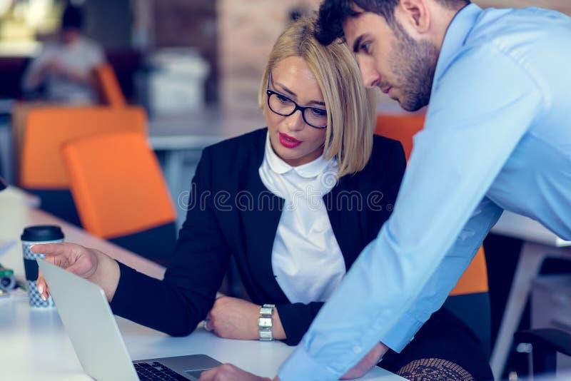 El CEO rubio profesional experto de la hembra que explica al empleado de sexo masculino joven requiere y estrategia fotos de archivo libres de regalías