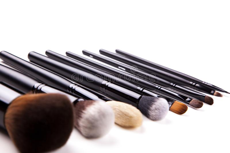 El cepillo profesional del maquillaje, diferente compone cepillos está en el fondo blanco clasificado en la línea imágenes de archivo libres de regalías