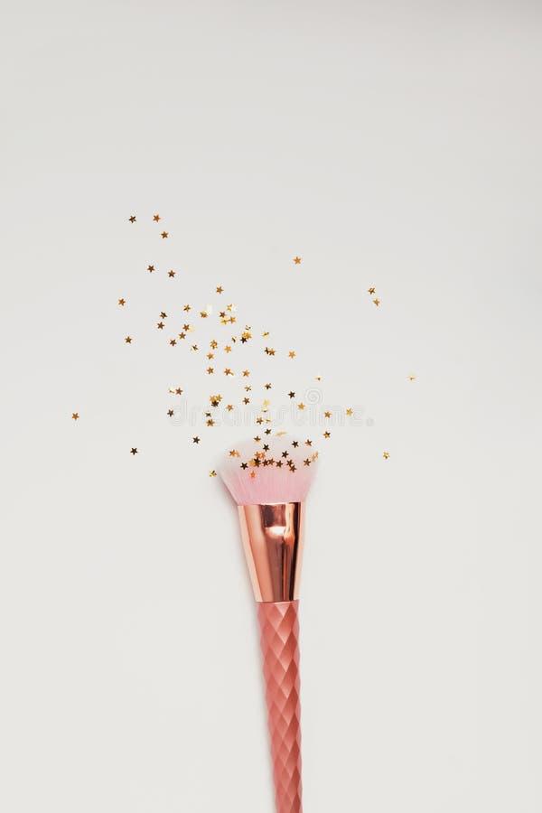El cepillo rosado del maquillaje con pequeño colden las estrellas en el fondo blanco imagenes de archivo