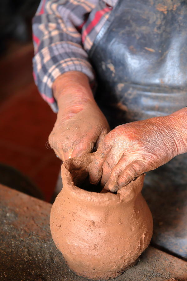 EL CERCADO, LA GOMERA, SPAIN - MARCH 23, 2017: detail of the hands of a woman making a traditional clay pot. Detail of the hands of a woman making a traditional royalty free stock photo