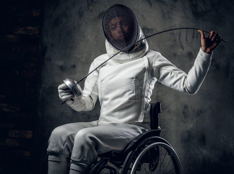 El cercador de sexo femenino en silla de ruedas sostiene el estoque fotos de archivo libres de regalías